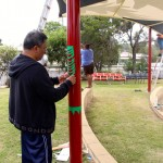 Rocko putting design on Shade sail poles
